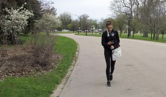 In this May 11, 2018 photo, Emily Mogavero, 17, looks at her cellphone while walking in Delaware Park in Buffalo, N.Y. The teenager said keeping up with social media and maintaining online profiles can make her stress levels rise but will put her phone out of reach or power it down to manage it. (AP Photo/Carolyn Thompson)