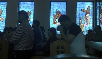 FILE - In this Aug. 13, 2017, file photo, worshippers attend Sunday Mass at Blessed Diego de San Vitores Church in Tumon, Guam. No doctors are willing to perform abortions in the U.S. territory of Guam, and the island's first female governor is concerned about the fallout. Gov. Lourdes Leon Guerrero fears women will seek illegal or dangerous alternatives after the last abortion provider retired last year. Abortion is legal in the heavily Catholic Pacific island, but doctors can deny services unless it's a medical emergency.(AP Photo/Tassanee Vejpongsa, File)