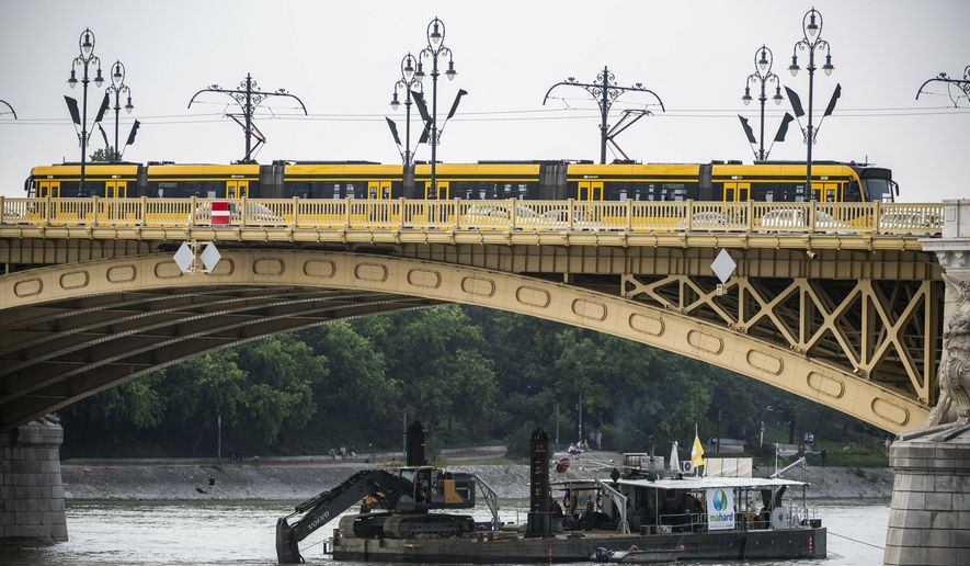 A power shovel fixed onto a pontoon works in Danube river near Margaret Bridge, the scene of a boat accident, in Budapest, Hungary, Thursday, June 6, 2019.  Search operations continue after a sightseeing boat carrying 33 South Korean tourists was crashed into by a large river cruise ship and sank on May 29, killing at least fifteen tourists. (Marton Monus/MTI via AP)