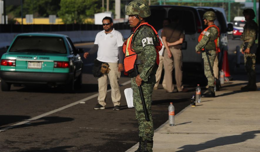 Migration officials and Military Police man a checkpoint on the highway, in Tapachula, Chiapas state, Mexico, Friday, June 7, 2019. President Donald Trump's threatened tariffs on Mexico are set to take effect Monday as planned, the White House said Friday, even as negotiators continued to meet to try to stave off his latest push to force the U.S. ally to stem the flow of Central American migrants into the United States. (AP Photo/Marco Ugarte)