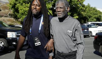 Former Golden State Warriors head coach Al Attles, right, walks toward Oracle Arena with his son Al Attles III before Game 4 of basketball's NBA Finals between the Warriors and the Toronto Raptors in Oakland, Calif., Friday, June 7, 2019. (AP Photo/Ben Margot)