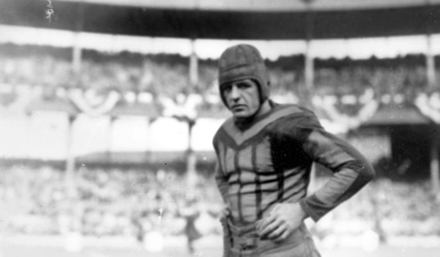 In this 1925, file photo, American football player Red Grange of the Chicago Bears is shown during a game against the New York Giants in New York. As the NFL enters its 100th season, what players wear on the field may have changed the most, going from leather helmets and long-sleeved turtlenecks and sweaters to plastic helmets with jerseys and pants almost shrink-wrapped to fit.(AP Photo/File)