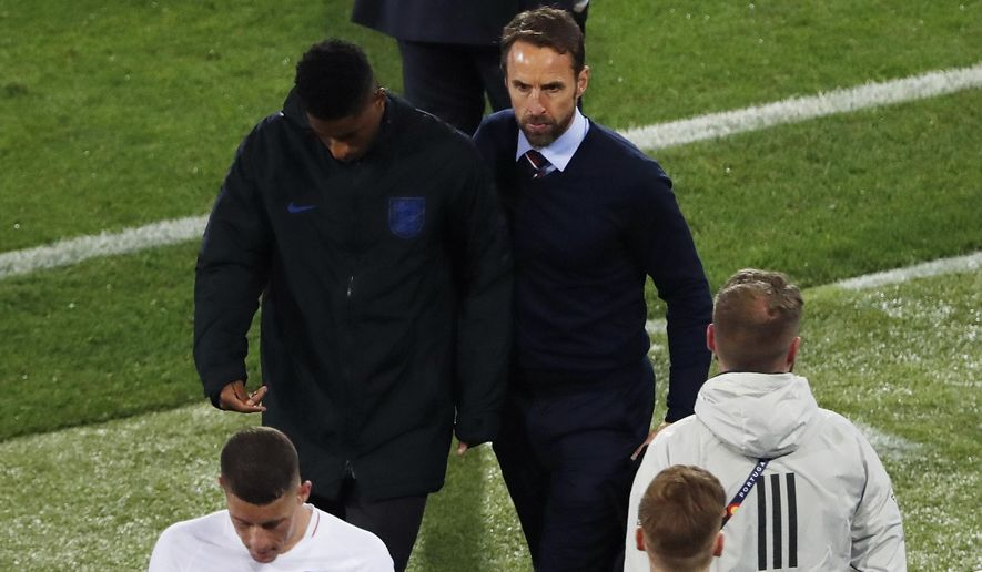 England manager Gareth Southgate, right, and England's Marcus Rashford, , center left, leave the pitch at the end of the UEFA Nations League semifinal soccer match between Netherlands and England at the D. Afonso Henriques stadium in Guimaraes, Portugal, Thursday, June 6, 2019. (AP Photo/Armando Franca)