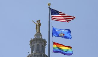 A rainbow flag observing Pride Month is displayed over the east wing of the Wisconsin State Capitol in Madison, Wis., Friday, June 7, 2019. The display, endorsed by Democratic Gov. Tony Evers, drew backlash from conservative Republican lawmakers who said it was divisive, while Democrats hailed it as a sign of inclusivity. (John Hart/Wisconsin State Journal via AP)  **FILE**