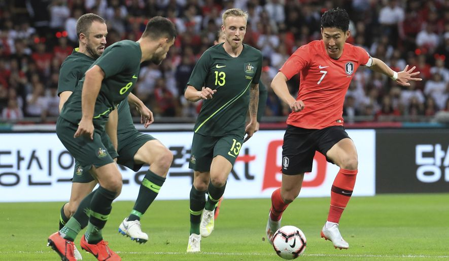 South Korea's Son Heung-min, right, is challenged by Australia's Bailey Wright, left, and James Jeggo, second right, during a friendly soccer match between South Korea And Australia at the Busan Asiad Main Stadium in Busan, South Korea, Friday, June 7, 2019. (Han Jong-chan/Yonhap via AP)