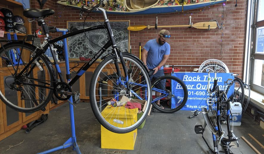 Samuel Ellis inspects a bike at his kayak and bicycle tour and rental company, on Thursday, June 6, 2019, in Little Rock, Arkansas. High waters in the central U.S. has forced some businesses and main streets to close or wait out the floods until tourism and recreation pick back up. (AP Photo/Hannah Grabenstein)