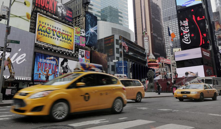 FILE - This Feb. 27, 2014 file photo shows New York City taxis passing through New York's Times Square. A New York man who talked about wanting to throw a grenade in Times Square has been arrested and is expected to be arraigned Friday on weapons-related charges, law enforcement officials told The Associated Press. (AP Photo/Richard Drew, File)