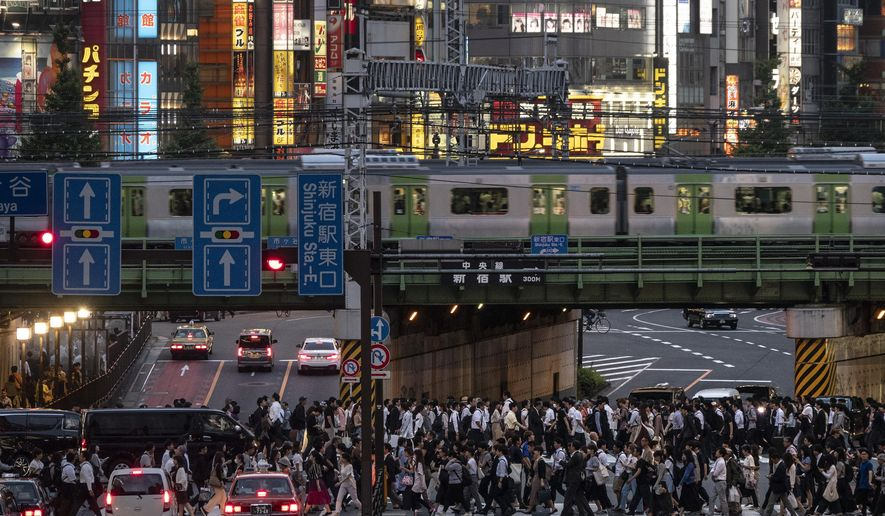 In this Tuesday, June 4, 2019, photo, a Yamanote Line train travels above commuters walking across the crossing during evening rush hours in the Shinjuku district of Tokyo. Operated by the East Japan Railway Co., the Yamanote Line in Tokyo makes a loop around the center of the city, connecting 29 stations that include key stops such as Shinjuku, Shibuya and Ikebukuro. A complete loop of about an hour offers scenes of Japanese daily lives. (AP Photo/Jae C. Hong)