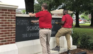 University of Alabama employees remove the name of Hugh F. Culverhouse Jr. off the School of Law sign in Tuscaloosa, Ala., Friday, June 7, 2019. The University of Alabama board of trustees voted Friday to give back a $26.5 million donation to a philanthropist Hugh F. Culverhouse Jr., who recently called on students to boycott the school over the state's new abortion ban. (AP Photo/Blake Paterson)