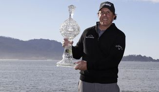 FILE - In this Feb. 11, 2019, file photo, Phil Mickelson poses with his trophy on the 18th green of the Pebble Beach Golf Links after winning the AT&T Pebble Beach Pro-Am golf tournament in Pebble Beach, Calif. At Pebble Beach, a course teeming with history for Mickelson, the 48-year-old, five-time major champion will come face to face with what might be his last, best chance to win the U.S. Open and become the sixth player to complete the career Grand Slam.  (AP Photo/Eric Risberg, File)