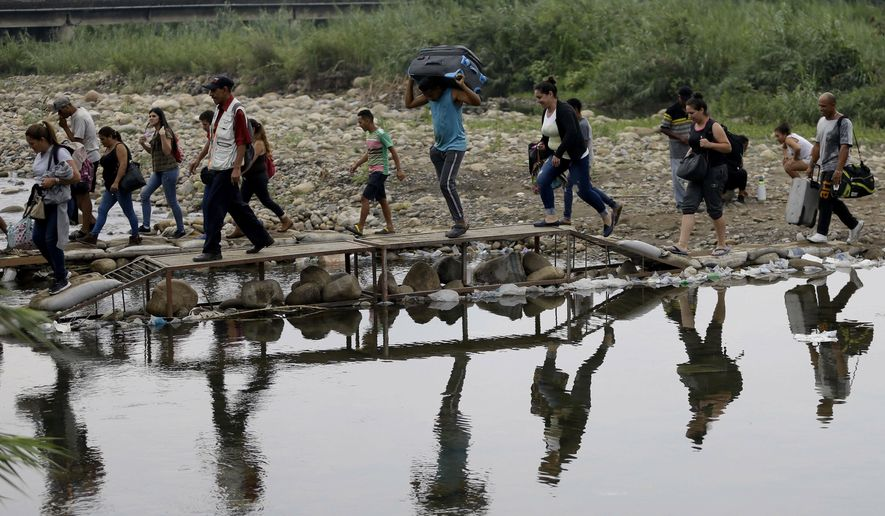 FILE - In this April 14, 2019 file photo, Venezuelans cross illegally into Colombia near the Simon Bolivar International Bridge, close to Cucuta, Colombia. The U.N. refugee agency said Friday, June 7, that the number of Venezuelans who have left their country in recent years has surpassed 4 million. (AP Photo/Fernando Vergara, File)