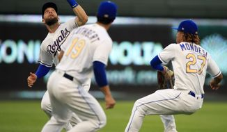 Kansas City Royals left fielder Alex Gordon, right, zeros in and catches a fly ball hit by Chicago White Sox Yoan Moncada during the third inning of a baseball game at Kauffman Stadium in Kansas City, Mo., Friday, June 7, 2019. Kansas City Royals third baseman Cheslor Cuthbert (19) and shortstop Adalberto Mondesi (27) avoid a collision on the play. (AP Photo/Orlin Wagner)