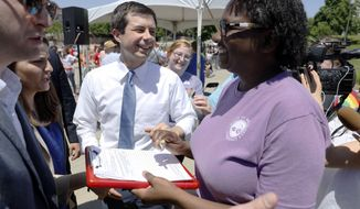 Democratic presidential candidate Pete Buttigieg signs an autograph during the Capital City Pride Fest, Saturday, June 8, 2019, in Des Moines, Iowa. (AP Photo/Charlie Neibergall)