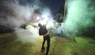 A demonstrator throws a flare toward Albanian police officers during an anti-government protest in Tirana, Albania, Saturday, June 8, 2019. Thousands of Albanian opposition supporters are gathering in an anti-government protest while the United States and the European Union caution their leaders to disavow violence and sit in a dialogue to overcome the political crisis. (AP Photo/Hektor Pustina)