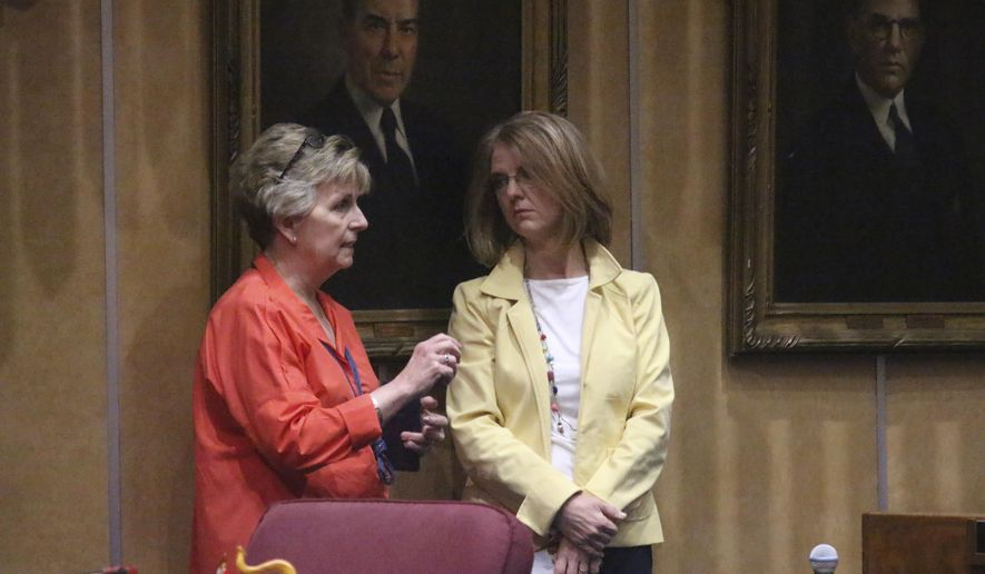 FILE - In this May 10, 2019, file photo, Republican Sens. Kate Brophy McGee, left, and Heather Carter, confer on the state Senate floor in Phoenix. Brophy McGee and Carter were responsible for the defeating a bill setting up a program to dissuade women from seeking abortions pushed by Cathi Herrod, who leads the powerful social conservative group Center for Arizona Policy. (AP Photo/Bob Christie)