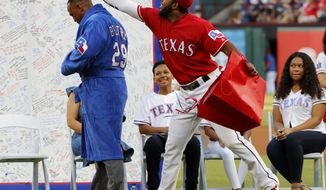 Retired Texas Rangers player Adrian Beltre tries on a gift presented to him by the team as shortstop Elvis Andrus reaches for his head during a jersey retirement ceremony for Beltre before the second baseball game of a doubleheader against the Oakland Athletics in Arlington, Texas, Saturday, June 8, 2019. (AP Photo/Tony Gutierrez)