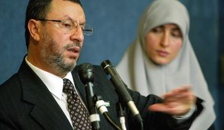 FILE - In this Feb. 16, 2004 file photo,  Abdelhaleem Ashqar, left, with his wife Asma, right, meets reporters at the National Press Club in Washington, to announce his presidential candidacy for the Palestinian National Authority.  Ashquar who says he fears torture at the hands of Israeli authorities,  is back in the U.S. after a judge's order forced immigration authorities to reverse his deportation and bring him back from Israel before he ever got off the plane.  According to court papers and interviews, U.S. authorities arrested and deported Ashqar Tuesday, June 4, 2019  after misleading him about his need to report to an immigration office to process paperwork.  (AP Photo/Pablo Martinez Monsivais, File)