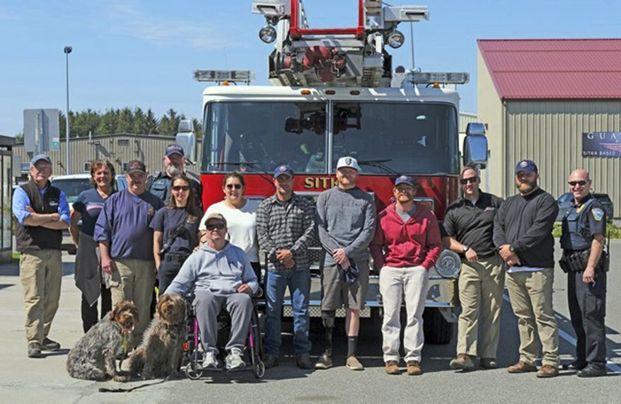 In this Saturday, May 25, 2019 photo, military veterans from Freedom Alliance are greeted at the Sitka, Alaska, airport by local fire and police personnel as they start a week of adventure at Vonnie's Charters and Halibut Point Lodge. Often overlooked in conflicts that occur thousands of miles away on continents most people see just on social media, are the military veterans who return to their non-service lives with traumas both visible and unseen. A local fishing charter business, working with a veteran support organization called Freedom Alliance, has been reaching out to these veterans over the past several years, giving them a taste of all that Alaska has to offer. (Klas Stolpe/Sitka Sentinel via AP)
