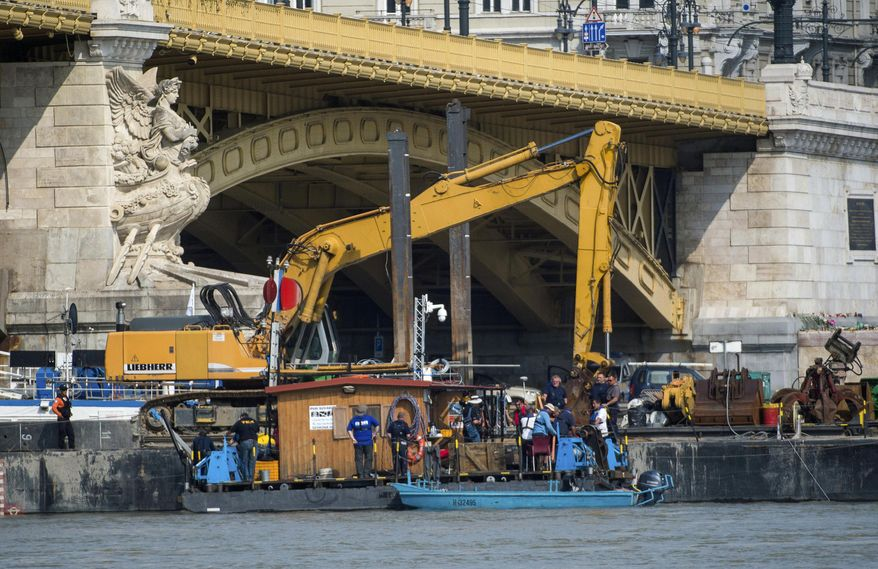 A dredger is stationed at Margaret Bridge during preparations to retrieve the shipwreck of the deadly boat accident in Budapest, Hungary, Friday, June 7, June 2019.  A sightseeing boat carrying some 33 South Korean tourists was crashed into by a large river cruise ship and sank on May 29, with 21 people still reported missing and salvage work hampered by poor conditions.  (Zoltan Balogh/MTI via AP)