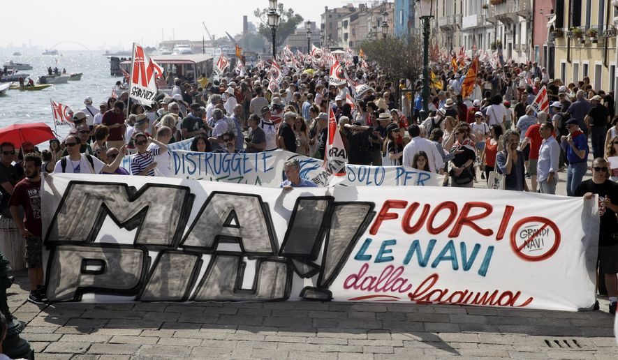 People march during a demonstration against cruise ships being allowed in the lagoon, in Venice, Italy, Saturday, June 8, 2019. Venice environmentalists have long complained that cruise ships displace water, wear down fragile foundations, cause air pollution and damage the delicate lagoon environment by dredging up the muddy bottom. (AP Photo/Luca Bruno)