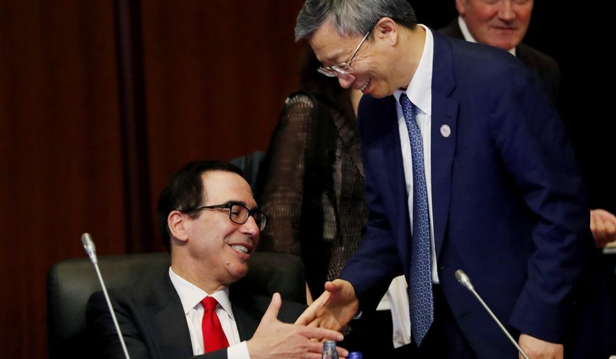 China's Central Bank Governor Yi Gang shakes hands with U.S. Treasury Secretary Steve Mnuchin, left, during the G20 Finance Ministers and Central Bank Governors Meeting Saturday, June 8, 2019, In Fukuoka, Japan. (Kim Kyung-hoon/Pool Photo via AP)