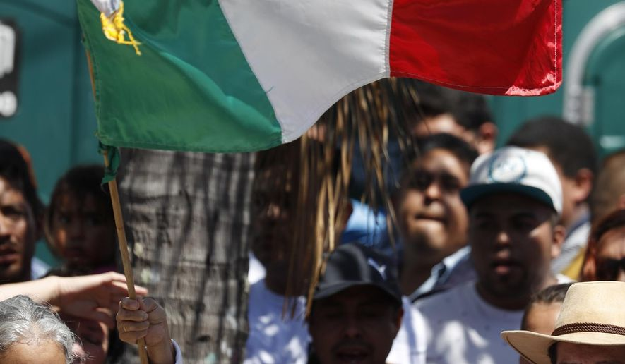 "A woman waves a Mexican flag prior to the speech by Mexican President Andres Manuel Lopez Obrador at a rally in Tijuana, Mexico, Saturday, June 8, 2019. Mexican President Andres Manuel Lopez Obrador will hold the rally in Tijuana even as President Trump has put on hold his plan to begin imposing tariffs on Mexico on Monday, saying the U.S. ally will take ""strong measures"" to reduce the flow of Central American migrants into the United States. (AP Photo/Eduardo Verdugo)"