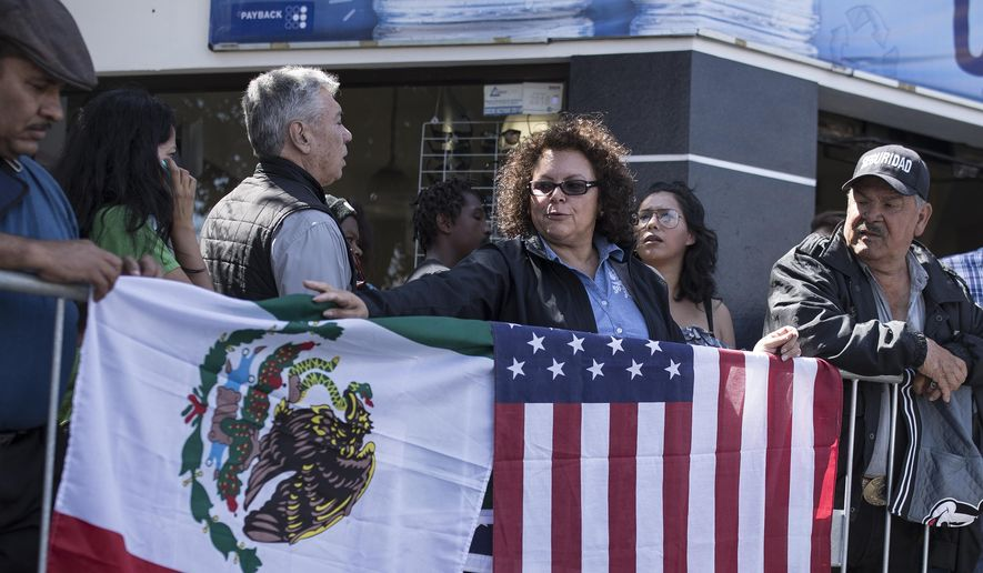 "Lilia Lara, a Tijuana resident, displays the U.S. and Mexican flags at the plaza where Mexican President Andres Lopez Obrador is to hold a rally in Tijuana, Mexico, Saturday, June 8, 2019. President Trump has put on hold his plan to begin imposing tariffs on Mexico on Monday, saying the U.S. ally will take ""strong measures"" to reduce the flow of Central American migrants into the United States. Lara said she arrived early to get a good spot for the rally. (AP Photo/ Hans-Maximo Musielik)"