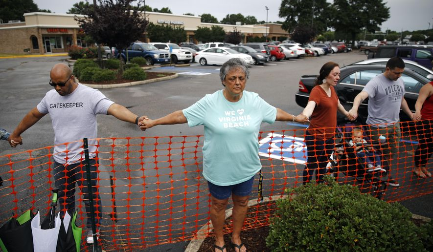 Lisa Dunaway, center, holds hands with other mourners during a vigil in response to a shooting at a municipal building in Virginia Beach, Va., Saturday, June 1, 2019. A longtime city employee opened fire at the building Friday before police shot and killed him, authorities said. (AP Photo/Patrick Semansky)