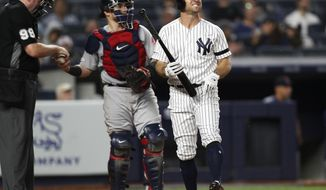 Home plate umpire Chris Conroy, left, gives a ball to Boston Red Sox catcher Christian Vazquez, center, as New York Yankees Brett Gardner, right, reacts during his at-bat in the seventh inning of a baseball game against the Boston Red Sox, Sunday, June 2, 2019, in New York. Gardner grounded out. (AP Photo/Kathy Willens)