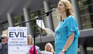 FILE - In this Tuesday, June 12, 2018 file photo, rape survivor and abuse victim advocate Mary DeMuth speaks during a rally protesting the Southern Baptist Convention's treatment of women outside the convention's annual meeting at the Kay Bailey Hutchison Convention Center in Dallas. On Tuesday, June 11, 2019, the Southern Baptist Convention gathers for its annual national meeting with one sobering topic _ sex abuse by clergy and staff _ overshadowing all others. (AP Photo/Jeffrey McWhorter)