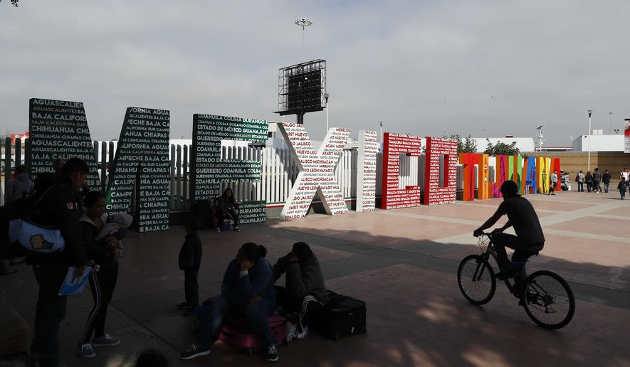 """The words """"Tijuana, Mexico"""" stand on the Mexican side of the border with the U.S. where migrants wait to be attended to apply for asylum in the U.S., in Tijuana, Mexico, Sunday, June 9, 2019. The mechanism that allows the U.S. to send migrants seeking asylum back to Mexico to await resolution of their process has been running in Tijuana since January, and one element of an agreement to head off Trump's threat of U.S. tariffs on all imports from Mexico is to extend that program across the entire border. (AP Photo/Eduardo Verdugo)"""