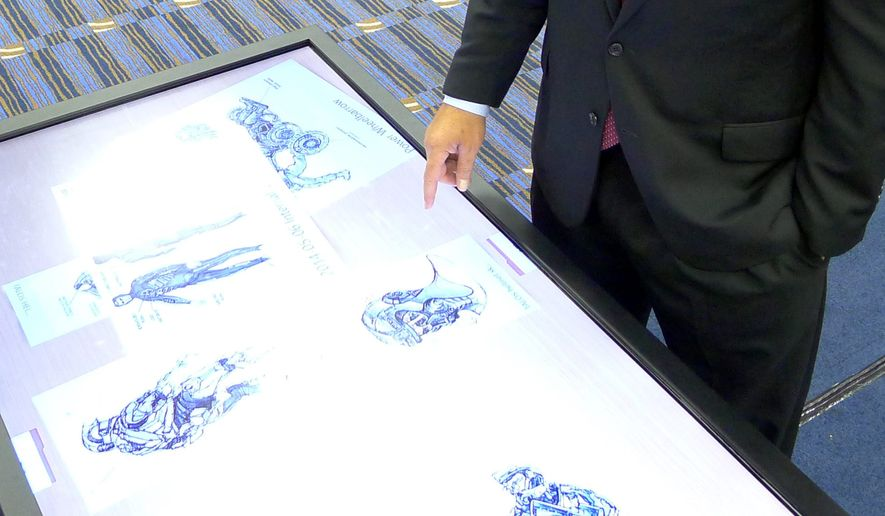 In this May 20, 2014, file photo, James Geurts, deputy for Acquisition of the U.S. Special Operations Command at MacDill Airforce Base, looks at sketches of the Tactical Assault Light Operator Suit (TALOS) during the Special Operations Forces Industry Conference in Tampa, Fla. (AP Photo/Tamara Lush)