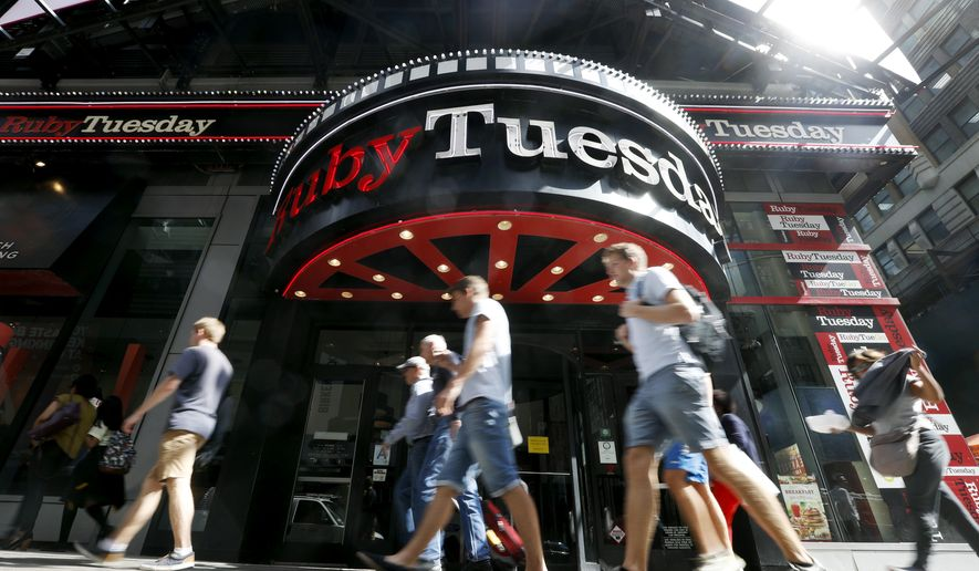 Visitors to New York's Times square walk past a Ruby Tuesday restaurant, Friday, Sept. 16, 2016. Customers have been walking away from sit-down chains as convenience and affordability take precedence. Ruby Tuesday said this week that its CEO is resigning, and the chain forecast another quarter of lower sales as it closes locations. It's the latest of several established restaurant groups that are retrenching, changing management or scrambling to adapt as people have more food choices all around them. (AP Photo/Mary Altaffer)