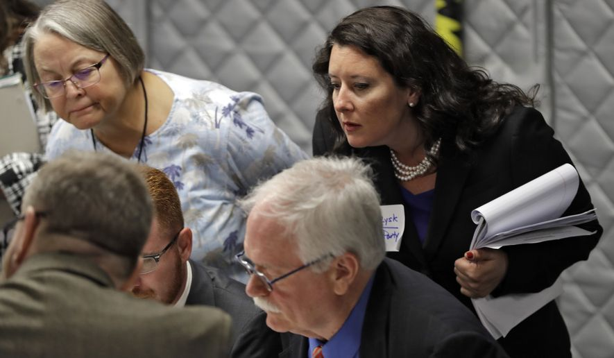 Democratic party observer Rachel May Zysk, right, looks on a volunteers check under and over votes during an elections manual recount for three undecided races Friday, Nov. 16, 2018, in Tampa, Fla.  Florida's bitter U.S. Senate contest is headed to a legally required hand recount after an initial review by ballot-counting machines showed Republican Gov. Rick Scott and Democratic Sen. Bill Nelson separated by less than 13,000 votes.  (AP Photo/Chris O'Meara)