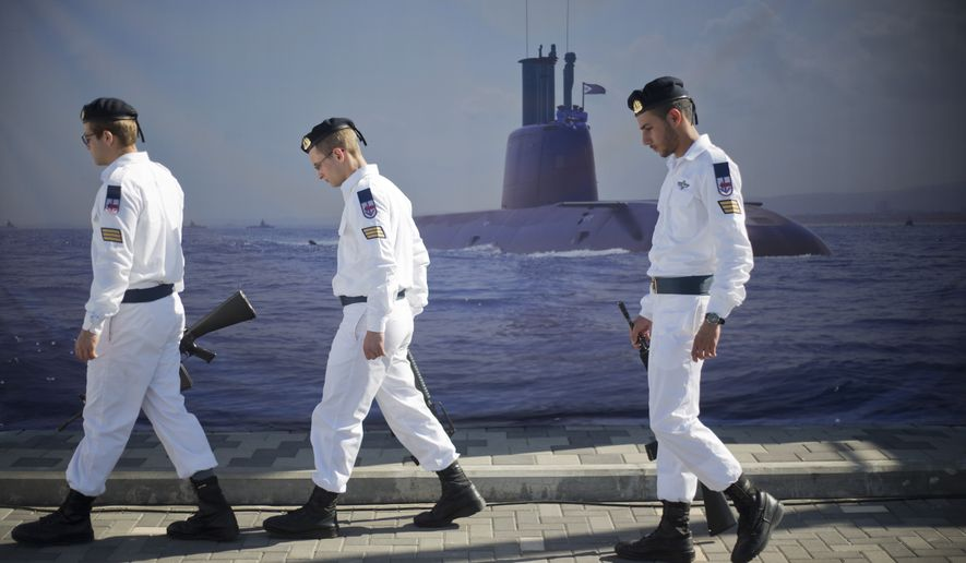 "Israeli naval soldiers honor guard walks past a poster of a submarine as they wait for the arrival of a new navy submarine ""Rahav"" in the military port in Haifa, Israel, Tuesday, Jan. 12, 2016. The vessel, which was built in Germany, reached Israel Tuesday. (AP Photo/Ariel Schalit)"