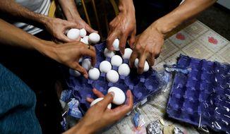 Migrants applying for asylum in the U.S. make breakfast on the border in Tijuana, Mexico. (Associated Press)