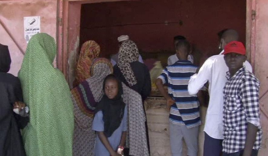 In this frame grab from video, people wait in line for bread outside a bakery in Khartoum, Sudan, Sunday, June 9, 2019. The first day of the workweek in Sudan saw shops closed and streets empty as part of a general strike called by protest leaders who are demanding the resignation of the ruling military council. The Sudanese Professionals Association had urged people to stay home to protest a deadly crackdown last week, when security forces violently dispersed the groups main sit-in camp outside the military headquarters in the capital of Khartoum. (AP Photo)