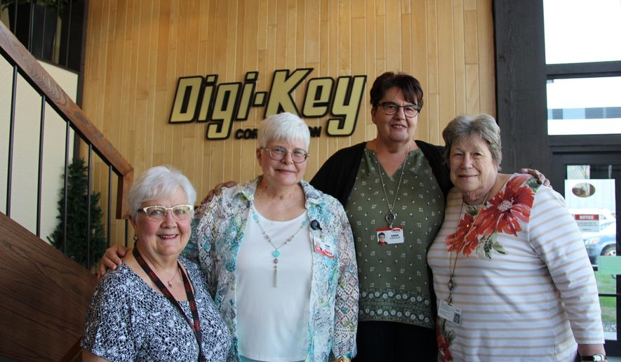 In this Tuesday, May 14, 2019 photo, from left, Evadell Tangquist, Leann Zander, Karen Konickson and Alice Wassink pose on a stairway at the Digi-Key headquarters in Thief River Falls, Minn. The four, who are employees at Digi-Key, say they are near or past retirement age, but plan to keep working, mostly because they like the work, the company and their coworkers. As the state's workforce ages, especially the large baby boomer generation, keeping on workers at retirement age could be more important to keeping jobs filled. (Peter Cox/Minnesota Public Radio via AP)