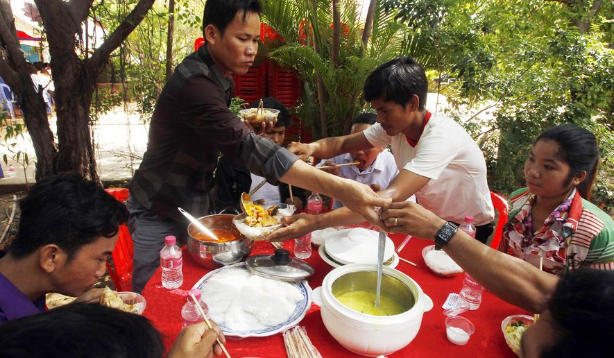 Cambodian garment workers eat noodle as their breakfast at a Buddhist pagoda at outside Phnom Penh, Cambodia, Sunday, June 9, 2019. The bitter decadeslong rivalry between Hun Sen, Cambodia's strongman leader, and Sam Rainsy, the self-exiled chief political rival and critic, has sometimes played out in deadly violence. But on Sunday, soup rather than blood was likely to be spilled. (AP Photo/Heng Sinith)