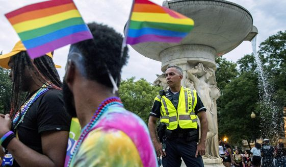 A police officer watches the crowd at the conclusion of the Capitol Pride Parade at Dupont Circle in Washington, Saturday, June 8, 2019. (AP Photo/Andrew Harnik)