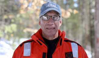 In this March 12, 2019 photo, Carl Watras poses in a survival suit jacket near Rock Lake in Vilas County, Wisc. Carl Watras, an limnologist for the University of Wisconsin-Madison's Center for Limnology, and the state Department of Natural Resources has been measuring mercury levels in Little Rock Lake in Vilas County, Wis., for 32 years. Watras found that mercury levels in the lake rise and fall with the water levels, which fluctuate due to climate change. (Sarah Whites-Koditschek/Wisconsin Center for Investigative Journalism via AP)