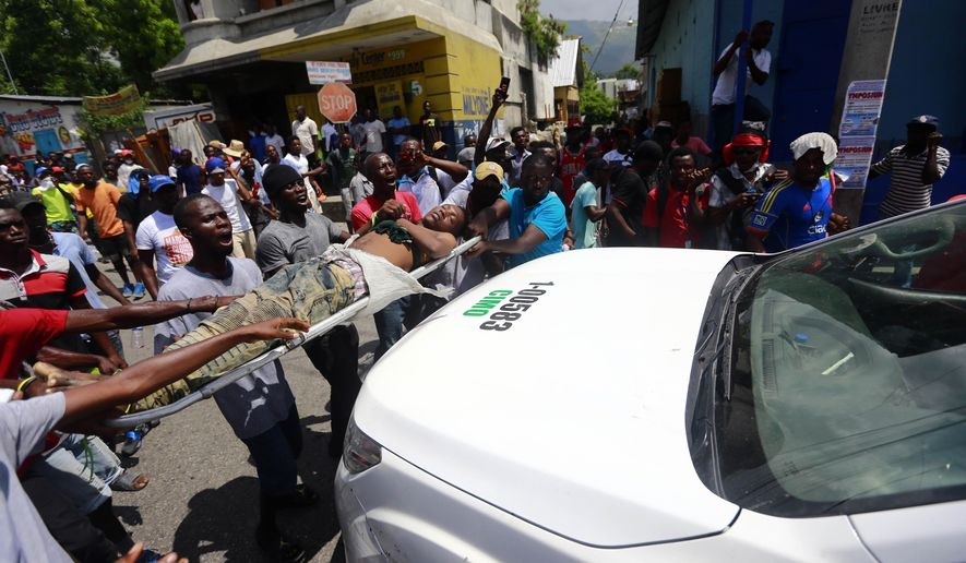 Protesters carry the body of man to a police vehicle, shouting blame at the police for his death, during an anti-government protest in Port-au-Prince, Haiti, Sunday, June 9, 2019. Protesters denouncing corruption paralyzed much of the capital as they demanded the removal of President Jovenel Moise. (AP Photo/Dieu Nalio Chery)