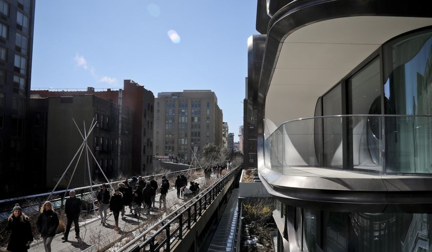In this March 5, 2019 photo, structures both modern and old flank visitors walking on the High Line park in New York. An estimated 8 million visitors a year now visit the park, which threads 1.5 miles through an utterly transformed part of Manhattan anchored at one end by the dazzling new home of the Whitney Museum of American Art and and at the other by Hudson Yards, a $25 billion development of skyscrapers, shops and a performing arts center. (AP Photo/Bebeto Matthews)
