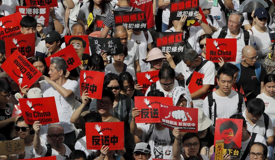 Protesters hold placards march in a rally against the proposed amendments to extradition law in Hong Kong, Sunday, June 9, 2019. The amendments have been widely criticized as eroding the semi-autonomous Chinese territory's judicial independence by making it easier to send criminal suspects to mainland China, where they could face vague national security charges and unfair trials. (AP Photo/Kin Cheung)