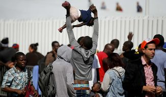 A migrant plays with his little girl as they wait to be attended to apply for asylum in the United States, at the border in Tijuana, Mexico, Sunday, June 9, 2019. The mechanism that allows the U.S. to send migrants seeking asylum back to Mexico to await resolution of their process has been running in Tijuana since January. (AP Photo/Eduardo Verdugo)
