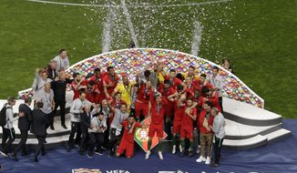 Portugal's Cristiano Ronaldo lifts up the trophy as he celebrates with players after winning the UEFA Nations League final soccer match between Portugal and Netherlands at the Dragao stadium in Porto, Portugal, Sunday, June 9, 2019. (AP Photo/Luis Vieira)