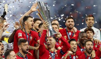 Portugal players celebrate with their trophy after defeating the Netherlands 1-0 in the UEFA Nations League final soccer match at the Dragao stadium in Porto, Portugal, Sunday, June 9, 2019. (AP Photo/Armando Franca)
