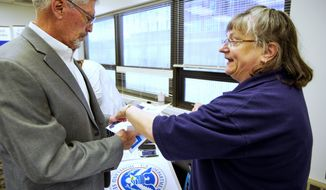 In this April 25, 2019 photo, FEMA representative Kristina Pooler, right, talks to Ned Holmes, National Guard Employment Support specialist, about available FEMA jobs, at a job fair in Lincoln, Neb. With federal disaster recovery staffers scrambling to meet needs amid floods, hurricanes and fires, they are now dealing with another issue _ historically low unemployment that's hampering their efforts to hire workers to help with the calamities. (AP Photo/Nati Harnik)