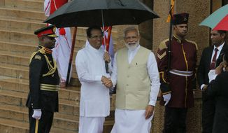 "Indian Prime Minister Narendra Modi, center is received by the Sri Lankan President Maithripala Sirisena, center left, upon his arrival at the presidential secretariat in Colombo, Sri Lanka, Sunday, June 9, 2019. Modi arrived in Sri Lanka on Sunday for a brief visit as part of his first overseas tour since reelection that emphasizes India's ""neighborhood-first"" policy. (AP Photo/Eranga Jayawardena)"