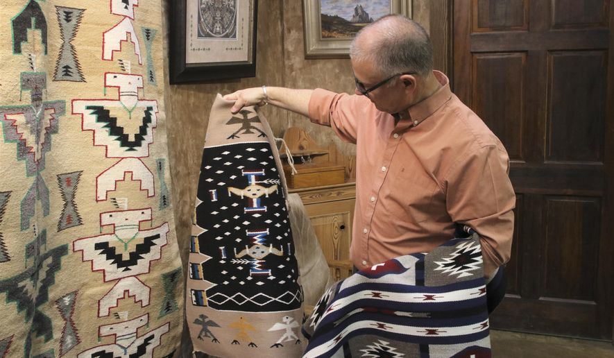 In this May 17, 2019 photo, Shiprock Trading Post owner Kent Morrow looks over rugs at his Farmington, N.M., business that operates under a model much different than the way trading posts traditionally have been run. The trading posts, once a staple in the Four Corners region that connected Navajo weavers and artists to buyers, are facing challenges to their survival. (Mike Easterling/The Daily Times via AP)